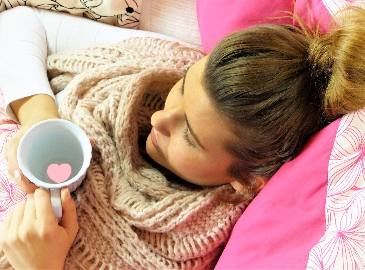 Woman sat on a sofa looking cosy with a mug of hot water with a heart floating in the mug