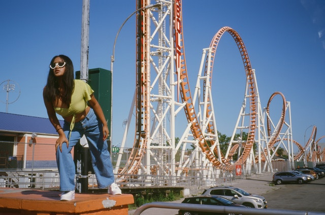 Lady in strong pose in front of a roller coaster